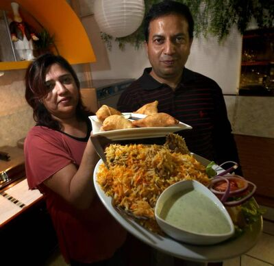 Humaira Asif (left) and Ali Mazhar pose with samosas(rear) and dumm biryani with chicken at the Green Chili.