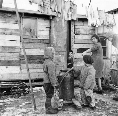 The Cardinal boys, seven-year-old Ronnie and five-year-old Frank, get ready to leave their Rooster Town shack and hike three-quarters of a mile for a can of water. Their mother talks to them while their two-year-old brother is seen peering out the shack door.