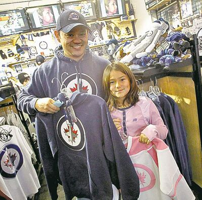 Jets fans Bruce Dueck and daughter Jesslyn, 9, check out the merchandise at the Jets Gear store before the start of the team's training camp.
