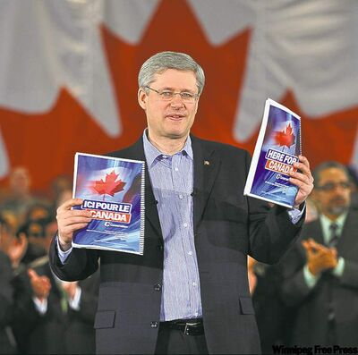 Stephen Harper holds up copies of Here for Canada, the Tory election platform.
