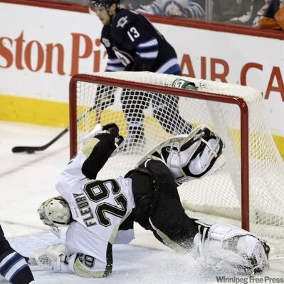 Pittsburgh Penguins' goaltender Marc-Andre Fleury (29) leaps across the net to try to get back into the play while Winnipeg Jets' Kyle Wellwood (13) looks to pass the puck in the first period.