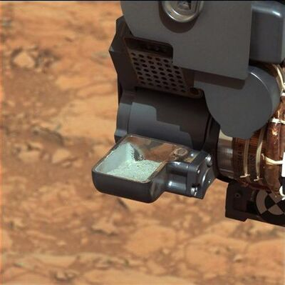 This image released by NASA shows the Curiosity rover holding a scoop of powdered rock on Mars. The rover recently drilled into a Martian rock for the first time and transferred a pinch of powder to its instruments to analyze the chemical makeup. (AP Photo/NASA)