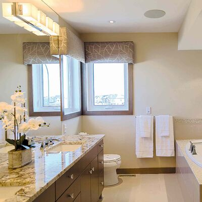 The ensuite is a peaceful, well-appointed space with a soaker tub, a beige porcelain tile floor, a glass tile shower and a portobello maple vanity.