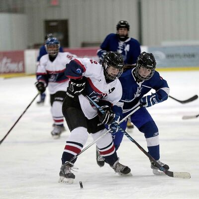 St. Mary's Academy's Clare Hibbert, left, and Selkirk Royal Anna Sternat battle for the puck.