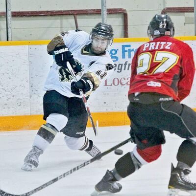 Bisons' Mike Hellyer shoots on the net against Dinos' Cory Pritz in their game Friday.