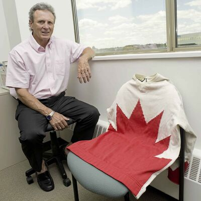 Former Team Canada player Paul Henderson poses with the jersey he wore in 1972 (CNS)