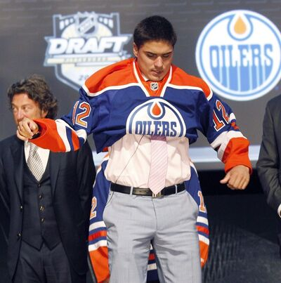 Nail Yakupov, a winger from Russia who was chosen first overall by the Edmonton Oilers in the first round of the NHL hockey draft, pulls on an Oilers jersey on Friday, June 22, 2012, in Pittsburgh. Yakupov could be forced to return to the Ontario Hockey League if he wants to continue playing during the NHL lockout. THE CANADIAN PRESS/AP-Keith Srakocic