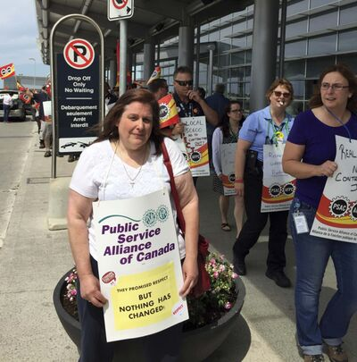 Union official Teresa Eschuk, poses with picket sign Friday during a noon-hour protest by support and maintenance workers over a contract dispute with the Winnipeg Airport Authority.</p>
