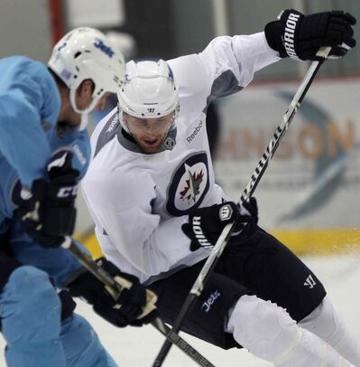 Winnipeg Jets' Blake Wheeler steers around teammate Adam Pardy  at practice Monday morning at the MTS Iceplex in Winnipeg.