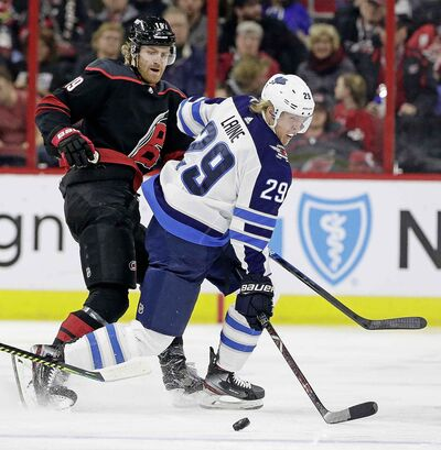 Carolina Hurricanes' Dougie Hamilton and Winnipeg Jets' Patrik Laine chase the puck during the first period.