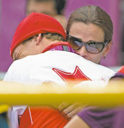 sean kilpatrick / the canadian pressCanada�s Simon Whitfield is hugged by his wife after crashing out of the men�s triathlon during the cycling segment at Hyde Park on Tuesday.