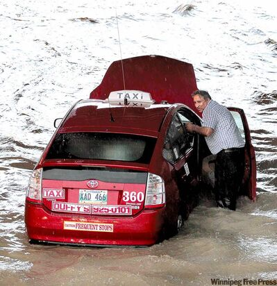 A cab stalled in deep water Saturday night in Winnipeg under the Jubilee Underpass on Pembina Highway after heavy rains.