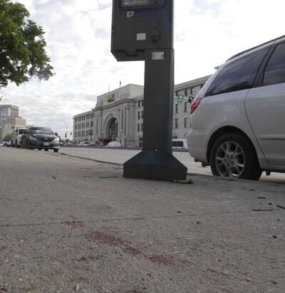 Blood stains the sidewalk Tuesday morning along Main Street across the from the Union Station after a stabbing incident that left one man in critical condition and another dead.