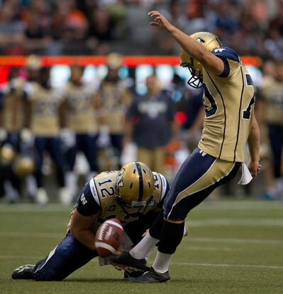 Winnipeg Blue Bombers' Lirim Hajrullahu, right, kicks a field goal as quarterback Brian Brohm holds against the B.C. Lions in Vancouver, B.C., on Friday July 25. He kicked five field goals during the 23-6 victory.
