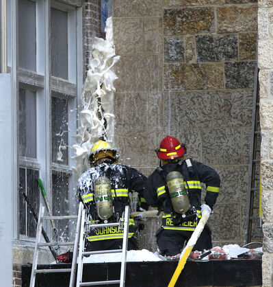 Winnipeg firefighters extinguish a fire within a the wall by a new addition under construction at the Glenelm School this morning.