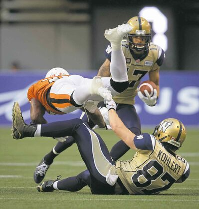 photos by darryl dyck / the canadian pressThe B.C. Lions� Dante Marsh (left) collides with Bombers Rory Kohlert as slotback Nick Moore carries the ball in the first half.