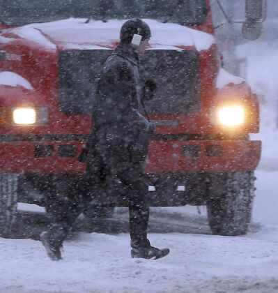 Pedestrians cross Portage Avenue as fresh snow falling creates low visibility conditions on the roads Thursday morning.