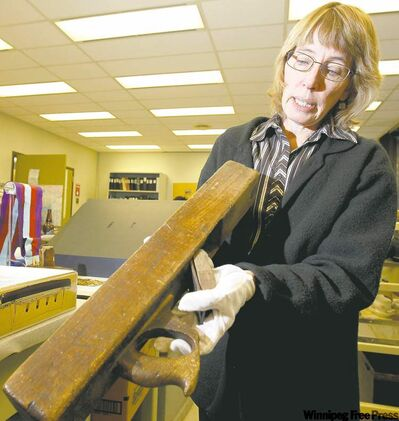 Sharon Reilly, Manitoba Museum curator, displays a carpenter's woodworking plane used to construct the Titanic.
