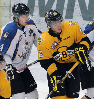 Brandonite Landon Cross of the Kootenay Ice checks Wheat Kings forward Ryley Lindgren in a game in Brandon last month.