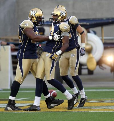 Blue Bombers' (left) Chris Greaves and No. 13 Chris Matthews celebrate the team's first touchdown against Montreal Thursday at Investors Group Field.
