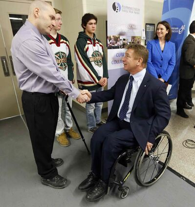 Rick Hansen (right) greets Scott Coates, a Manitoban who had a spinal-cord injury 22 years ago. Manitoba Health Minister Erin Selby (right) pledged spinal-cord research funds.
