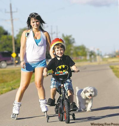 Sarah Gensorek, 23, with her four-year-old son, Seth, and dog, Rufus, on the Northeast Pioneers Greenway Trail between Gateway and Raleigh, in North Kildonan. Sarah and Seth try to get out to rollerblade and bicycle on the trail at least once or twice a week.