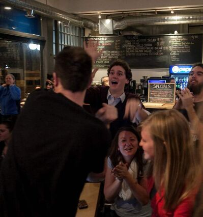 Burns Levi Garber (centre) high-fives other U.S. presidential election watchers after President Barack Obama was re-elected on Tuesday night. The Winnipeg Free Press News Café was packed with U.S. election junkies waiting for results.