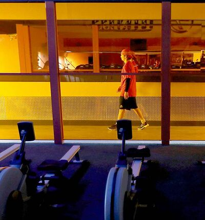 Egor Yakovlev walks past a row of exercise machines after a workout.