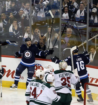 Winnipeg Jets' Bryan Little (18) and Andrew Ladd (16) celebrate after Little scored on Minnesota Wild goaltender Darcy Kuemper (35) during the first period.