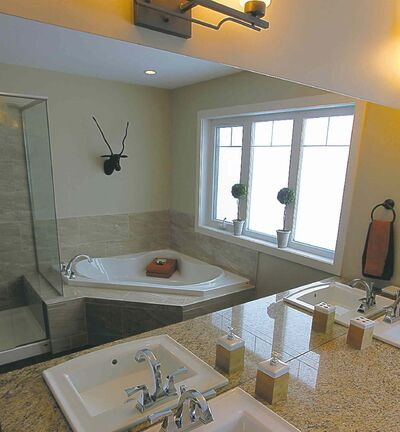 The big, bright and warm ensuite offers dark cork flooring, a corner soaker tub and shower featuring tempered glass and tile.