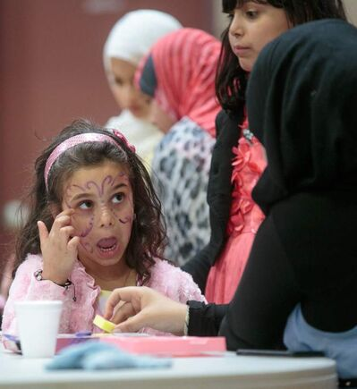 Samia Misbah has her face painted during a potluck celebrating Eid at the Grand Mosque on Waverley Street Thursday afternoon. The celebration was one of many in Winnipeg to mark the start of Eid and the end of Ramadan, the Islamic holy month of fasting.