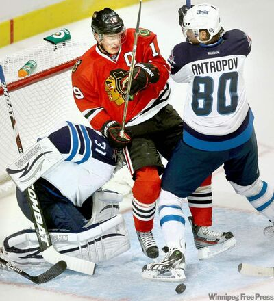 Chicago's Jonathan Toews gets slammed into Winnipeg Jets goaltender Ondrej Pavelec by Nik Antropov during first-period action Thursday night.