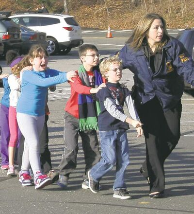 Connecticut State Police lead a line of children from the Sandy Hook Elementary School in Newtown, Conn. Friday. Twenty-seven people, including the shooter Adam Lanza, died at the scene.