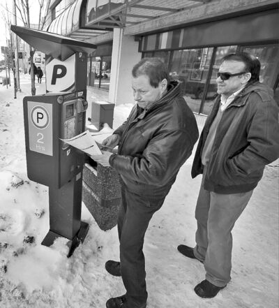Motorist Perry Rougeau tries a credit card seeking to pay his parking tab as Manaour Rajabi waits to try his luck.