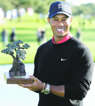 FULL CLOSE CUT CLOSECUT - Tiger Woods holds up the trophy after winning the Farmers Insurance Open golf tournament at the Torrey Pines Golf Course Monday, Jan. 28, 2013, in San Diego. It is Wood's seventh victory in the event. (AP Photo/Gregory Bull)