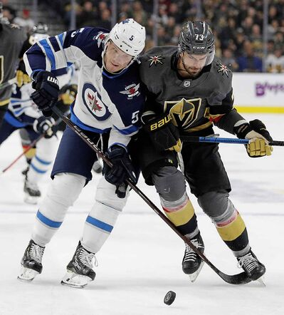Winnipeg Jets defenceman Dmitry Kulikov and Vegas Golden Knights centre Brandon Pirri vie for the puck during the second period.