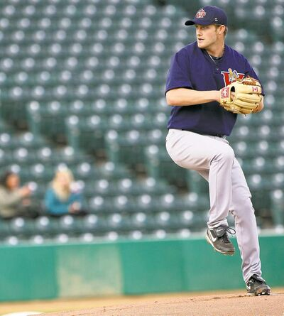 A fan watches as Fish hurler Mark Hardy delivers a pitch to a Winnipeg Wesmen hitter Friday night at Shaw Park.
