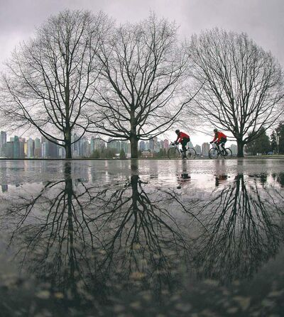 Cyclists ride through Stanley Park as rain falls in Vancouver, B.C.