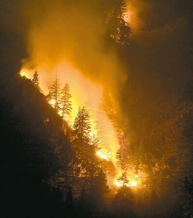Fire creeps down the western canyon wall above the Wood River in Hailey, Idaho, where crews battle the Beaver Creek Fire.