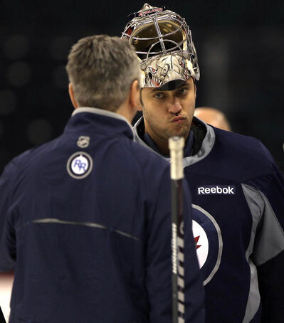 Winnipeg Jets goaltender Ondrej Pavelec chats with Jets goaltending coach Wade Flaherty at practice this morning.