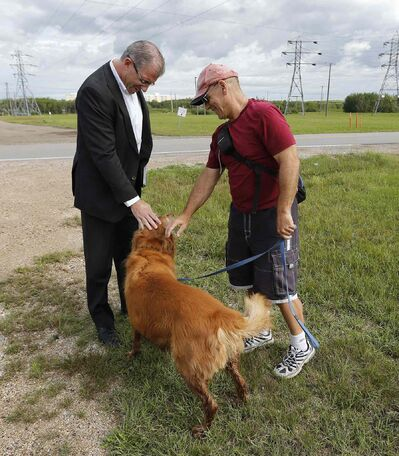 Gord Steeves talks with Robert Bagnercy and his dog Tucker near a dog park along the Parker lands — where the second leg of rapid transit would run — at Hurst Way.