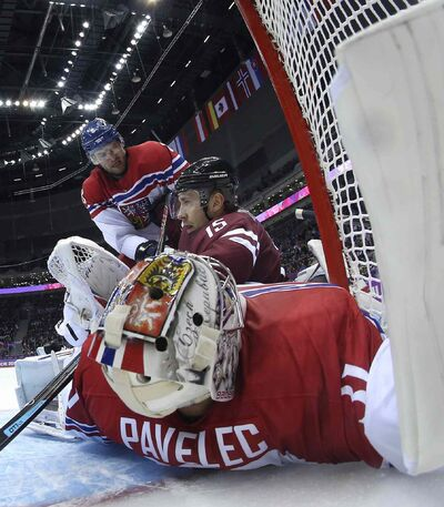 Czech Republic goaltender Ondrej Pavelec falls into the net as Latvia forward Martins Karsums collides with him in the second period of a men's ice hockey game at the 2014 Winter Olympics on Friday, Feb. 14, 2014, in Sochi, Russia.