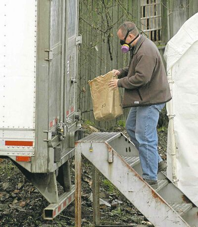 An investigator carries a paper bag to a refrigerated trailer for further  investigation.