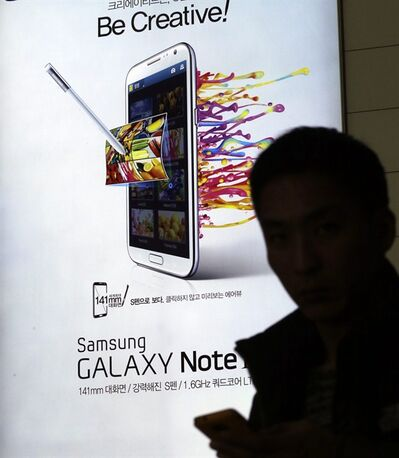 A man holds his mobile phone near an advertisement for Samsung Electronics' Galaxy Note II at Incheon International Airport in Incheon, west of Seoul, South Korea, Tuesday, Jan. 8, 2013. Samsung Electronics Co., the world's largest technology company by revenue, estimated Tuesday that its operating profit for the last quarter of 2012 nearly doubled to a record high, likely driven by continued smartphone momentum. (AP Photo/Lee Jin-man)