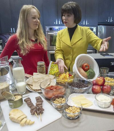 Ryan Remiorz / The Canadian Press</p><p>Health Minister Ginette Petitpas Taylor and nutritionist Jessica Cole look over samples from food groups at the unveiling of the new Canada's Food Guide. Critics point out that following the guide is difficult for people facing economic or geographic challenges.</p>