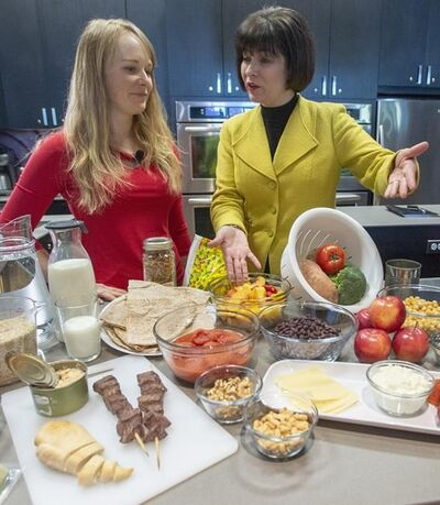 Health Minister Ginette Petitpas Taylor, right, and nutritionist Jessica Cole look over samples of some of the food groups at the unveiling of Canada's new Food Guide, Tuesday, January 22, 2019 in Montreal. A move by Ottawa to use Canada's food guide to drill home the dangers of chronic alcohol use caught some nutrition and addiction experts by surprise, but they welcomed the tougher stance on an issue they say demands a coordinated strategy.THE CANADIAN PRESS/Ryan Remiorz