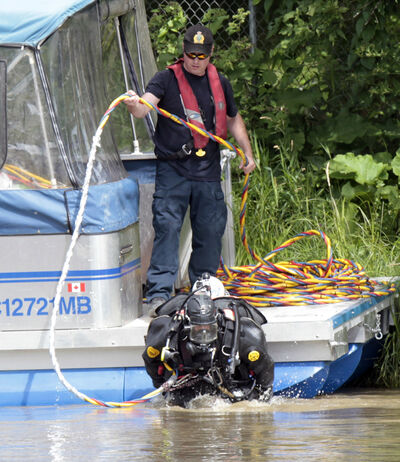 A WPS diver enters the Assiniboine River this morning.