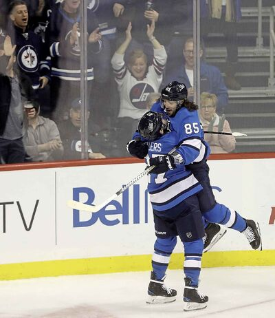 Winnipeg Jets' Nikolaj Ehlers lifts Mathieu Perreault as they celebrate Perreault's goal against the Chicago Blackhawks' during third period, Tuesday.