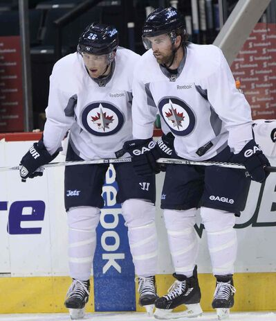 Jets Blake Wheeler (left) and Andrew Ladd take a breather during practice at the MTS Iceplex Tuesday.