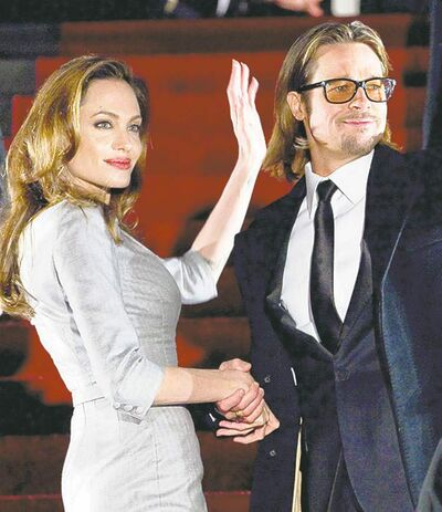 U.S. actress and director Angelina Jolie, left, and U.S. actor Brad Pitt, right, wave to the crowd as they arrive at the Cinema For Peace fundraising gala in Berlin Monday, Feb. 13, 2012. (AP Photo/Gero Breloer)